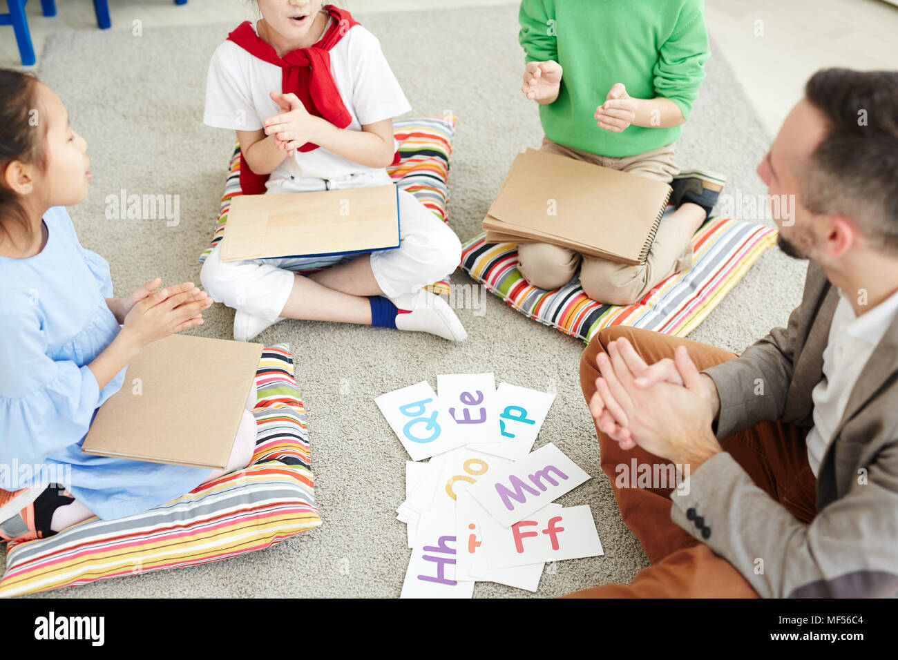 Primary school children and their male teacher sitting on the floor in classroom, playing games and learning alphabet letters - Stock Image