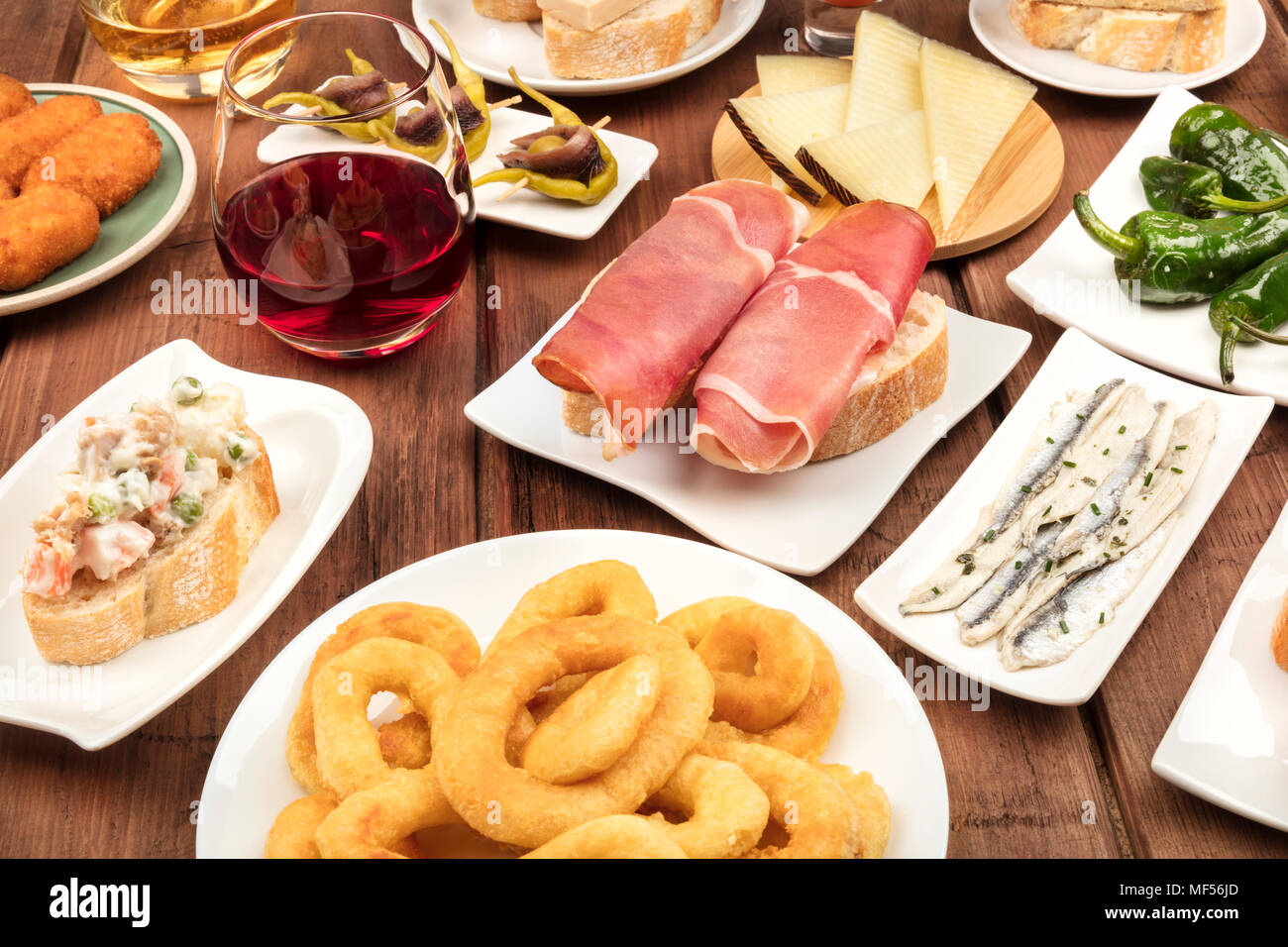 The food of Spain. A photo of many different Spanish tapas on a dark rustic texture. Jamon, cheese, wine, croquettes, calamari rings, anchovies and mo - Stock Image