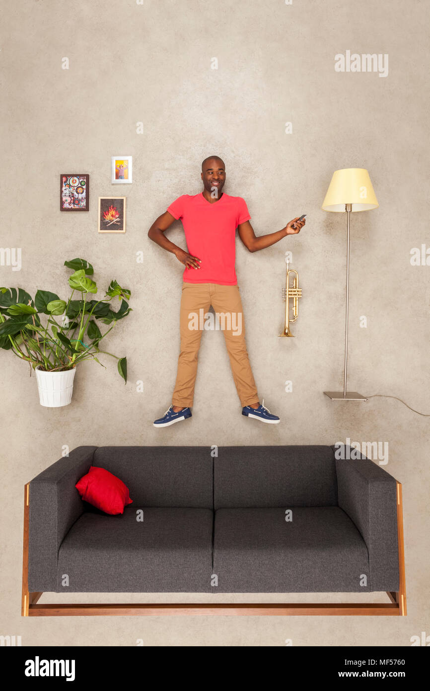 Man at home in his livingroom using smartphone,  listening music - Stock Image