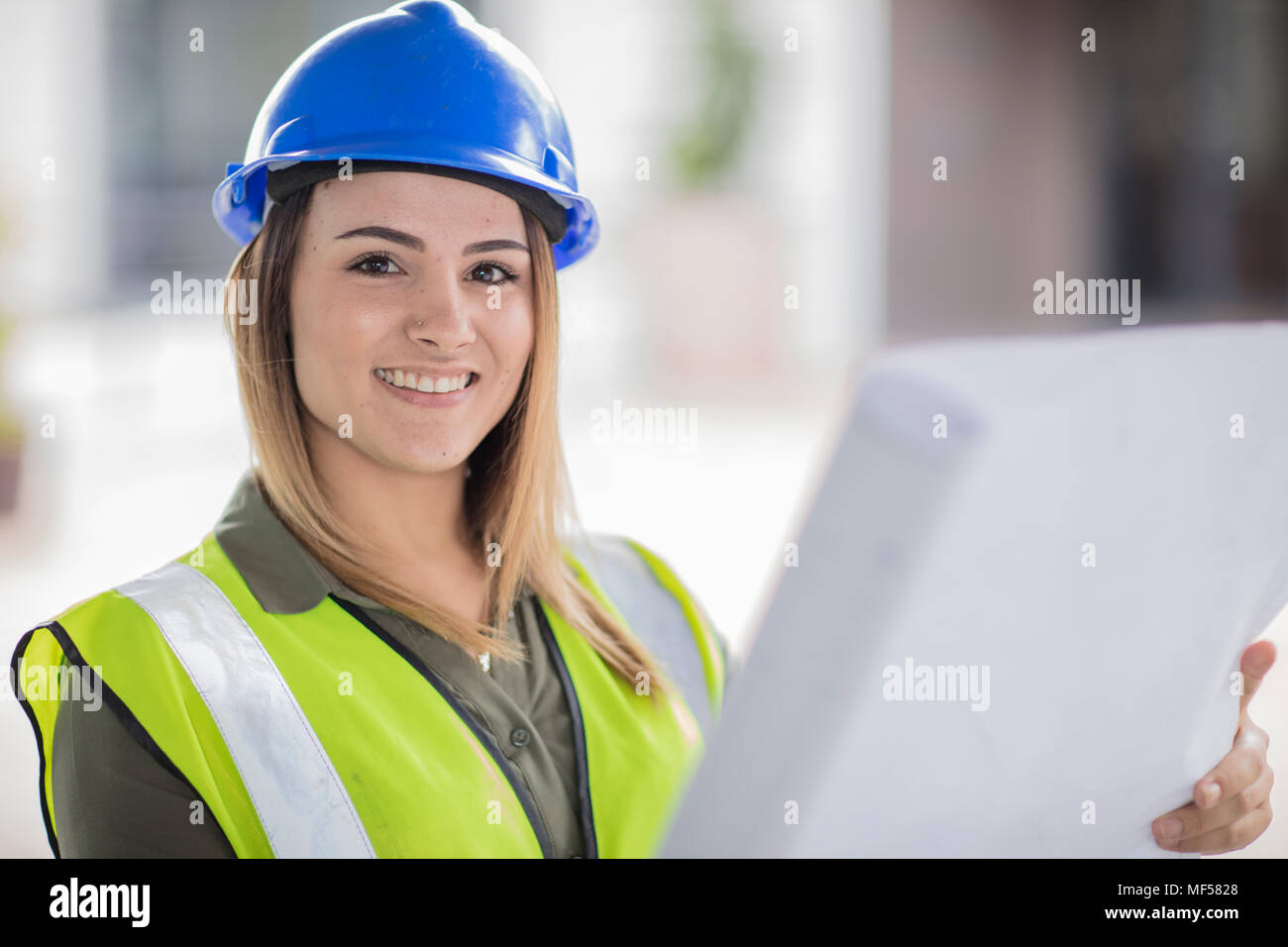 Portrait of smiling woman wearing hard hat and reflective jacket holding plan - Stock Image