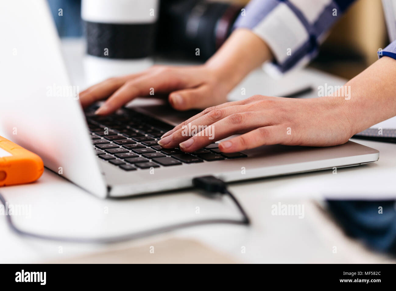 Close-up of woman using laptop at desk - Stock Image