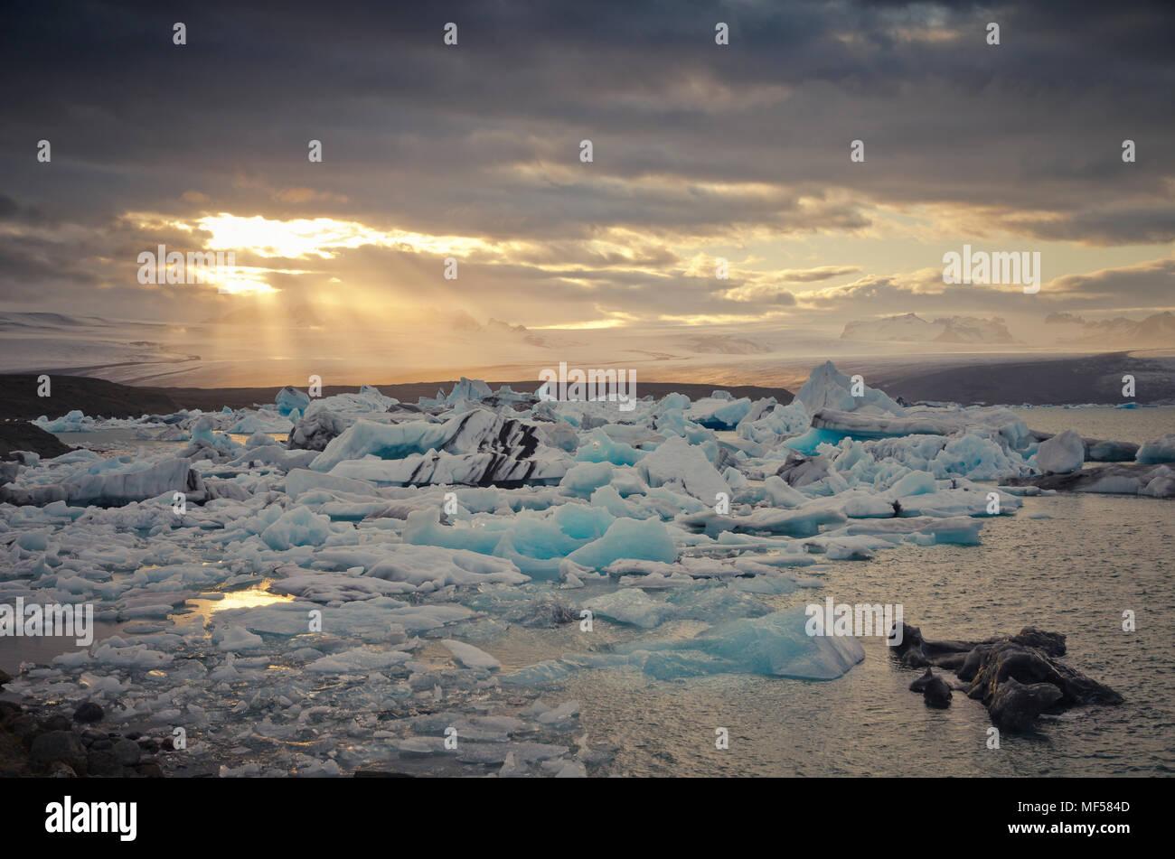 Iceland, South of Iceland, Joekulsarlon glacier lake, icebergs and sunshine through clouds - Stock Image