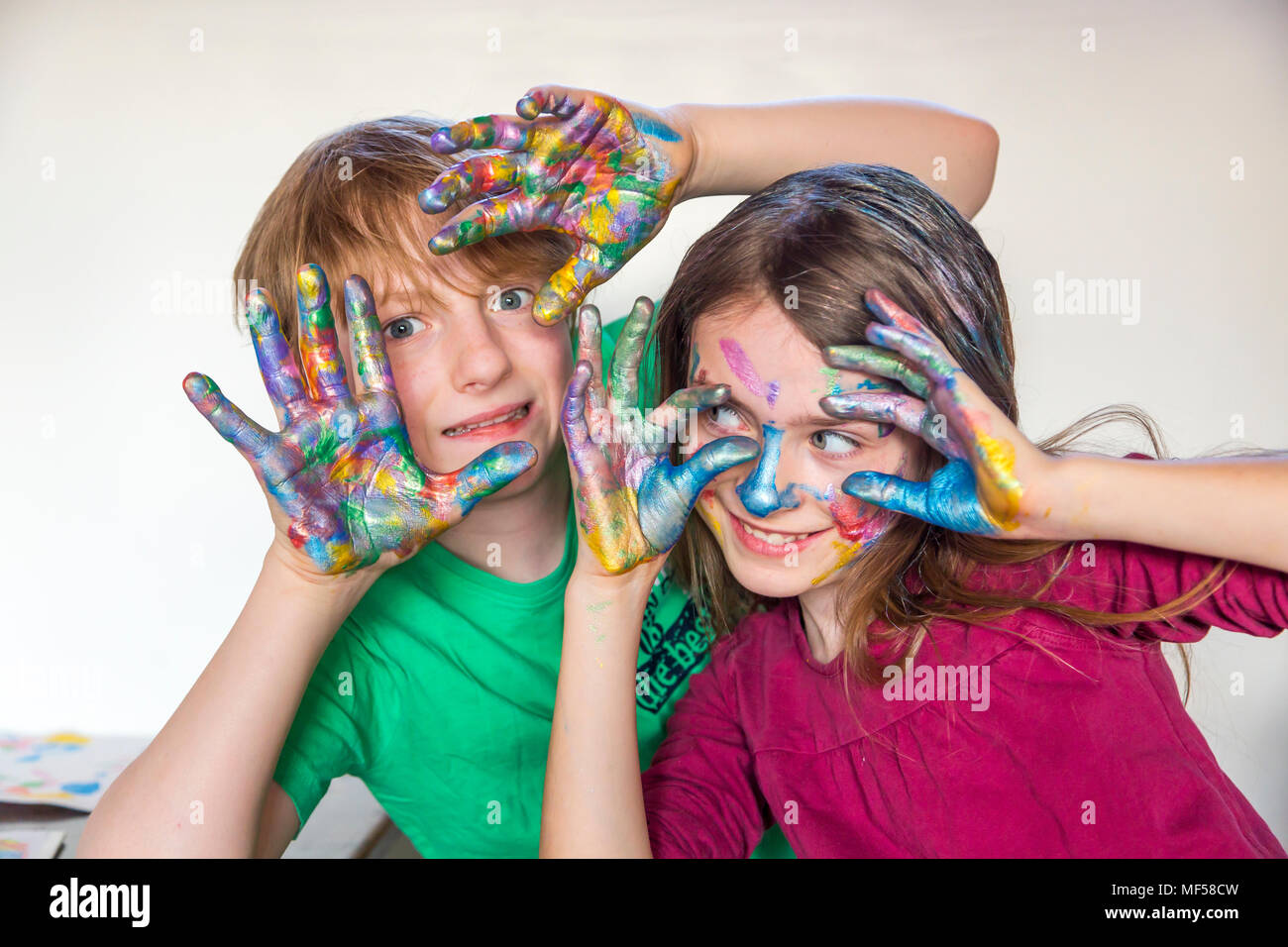 Boy And Girl Finger Paint On Hands
