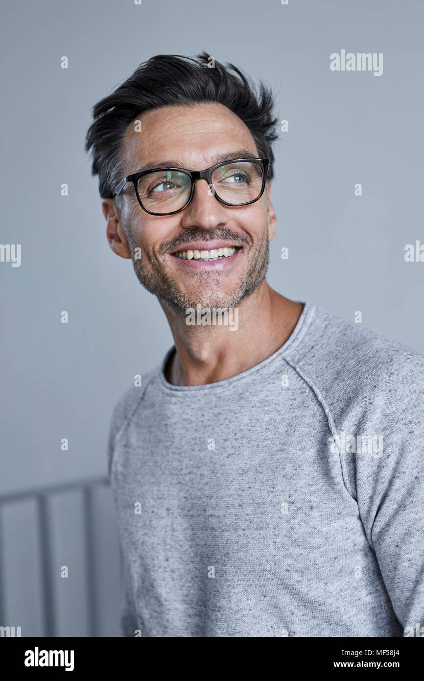 Portrait of laughing man with stubble wearing grey sweatshirt and glasses - Stock Image