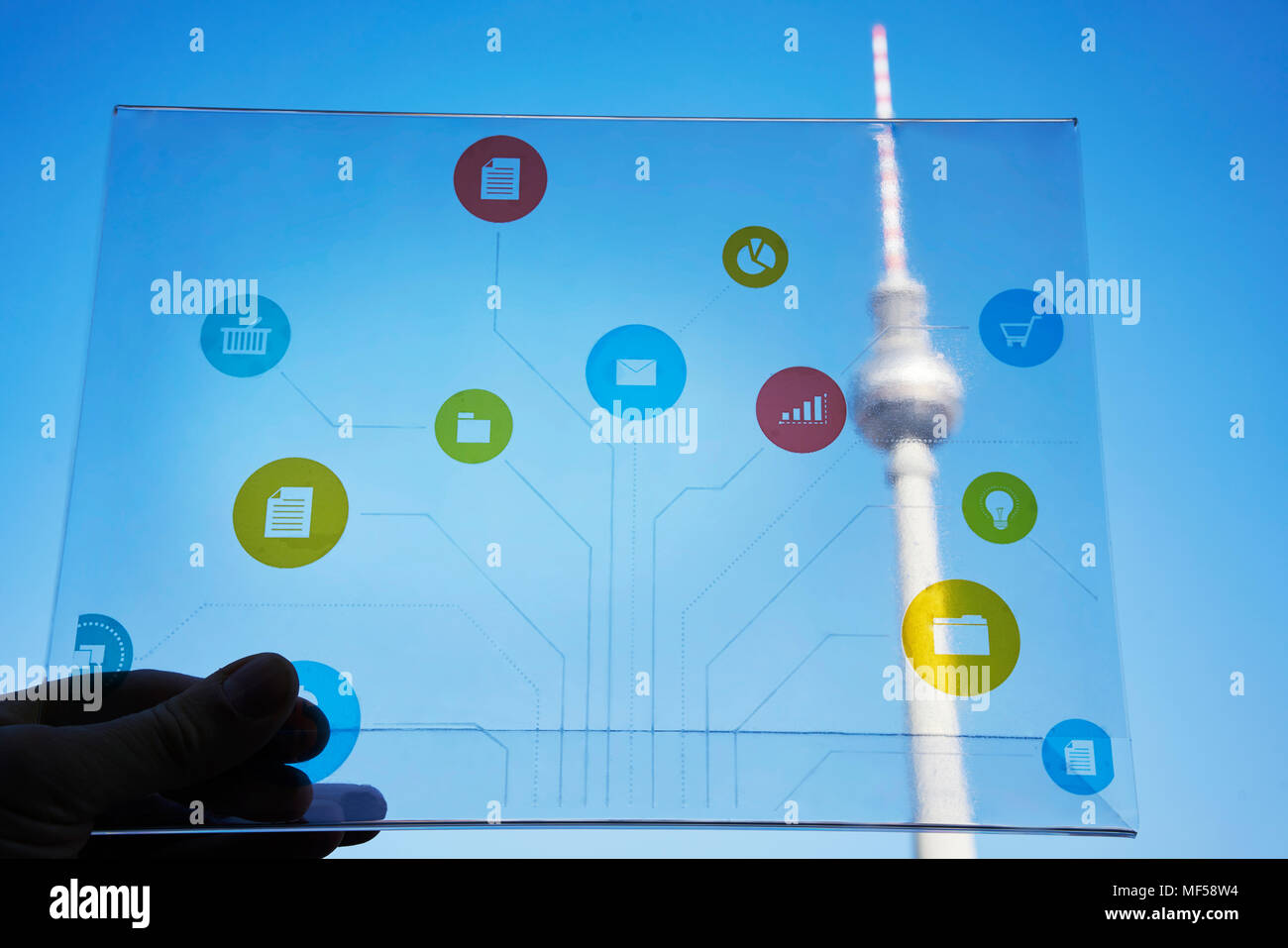 Germany, Berlin, hand holding futuristic device with digital icons in front of Tv tower - Stock Image