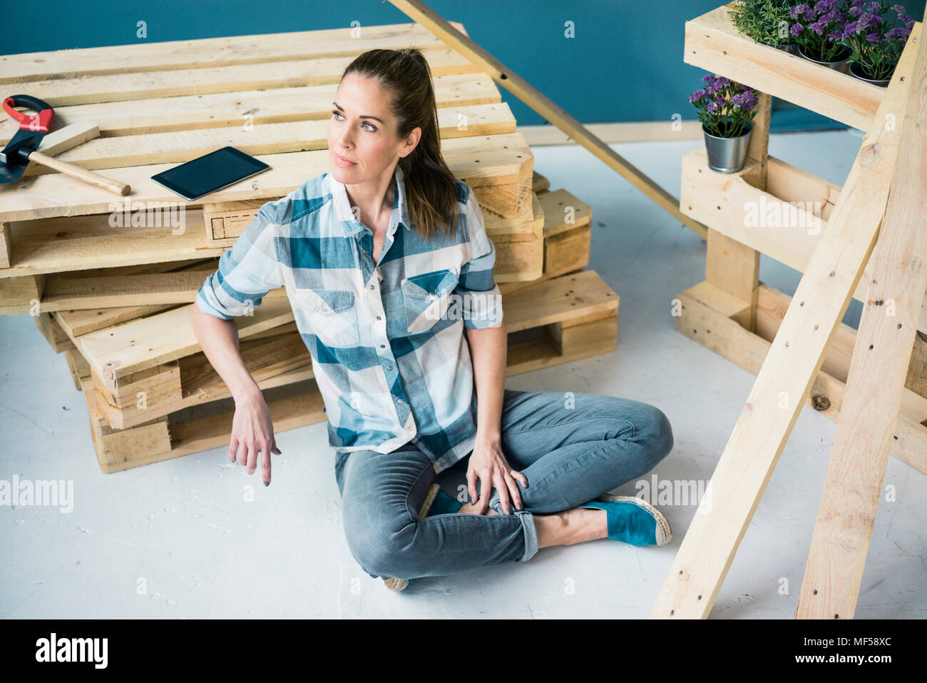 Beautiful woman planning to refurbish her home with pallets - Stock Image