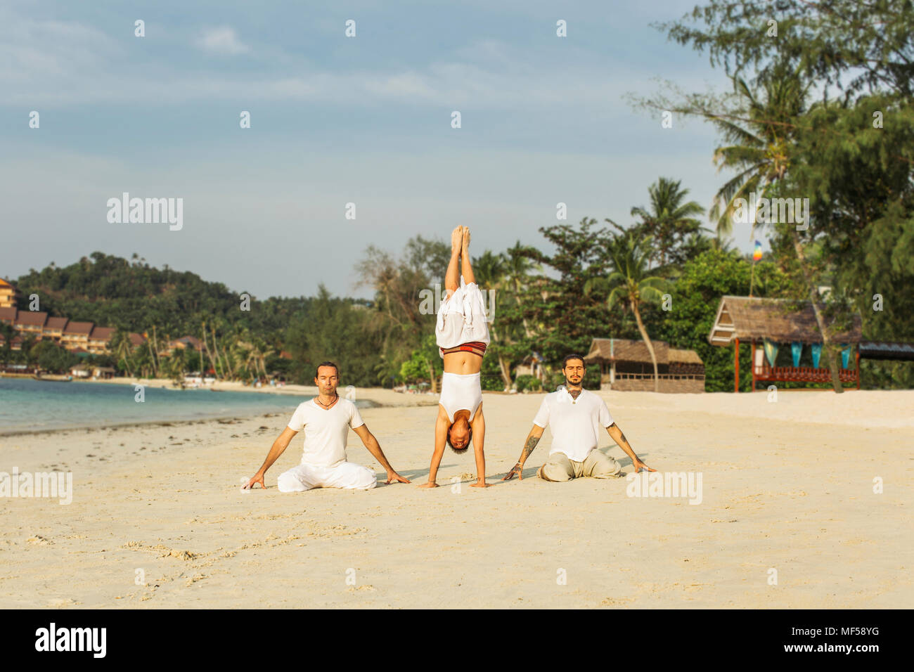 Thailand, Koh Phangan, three people doing yoga on a beach - Stock Image