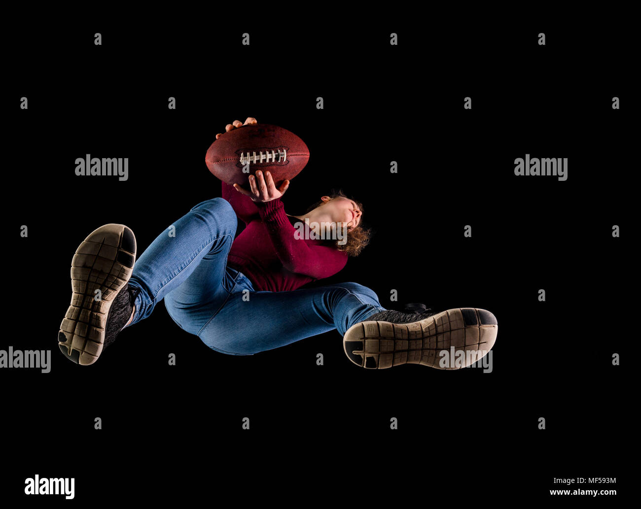Rugby player against black background seen from below - Stock Image