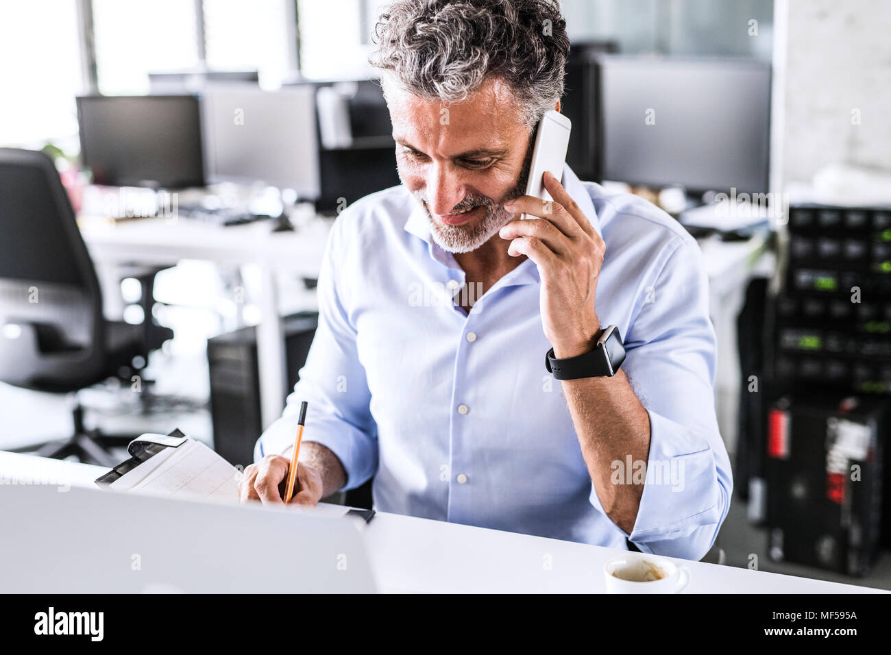 Smiling mature businessman sitting at desk in office talking on smartphone - Stock Image