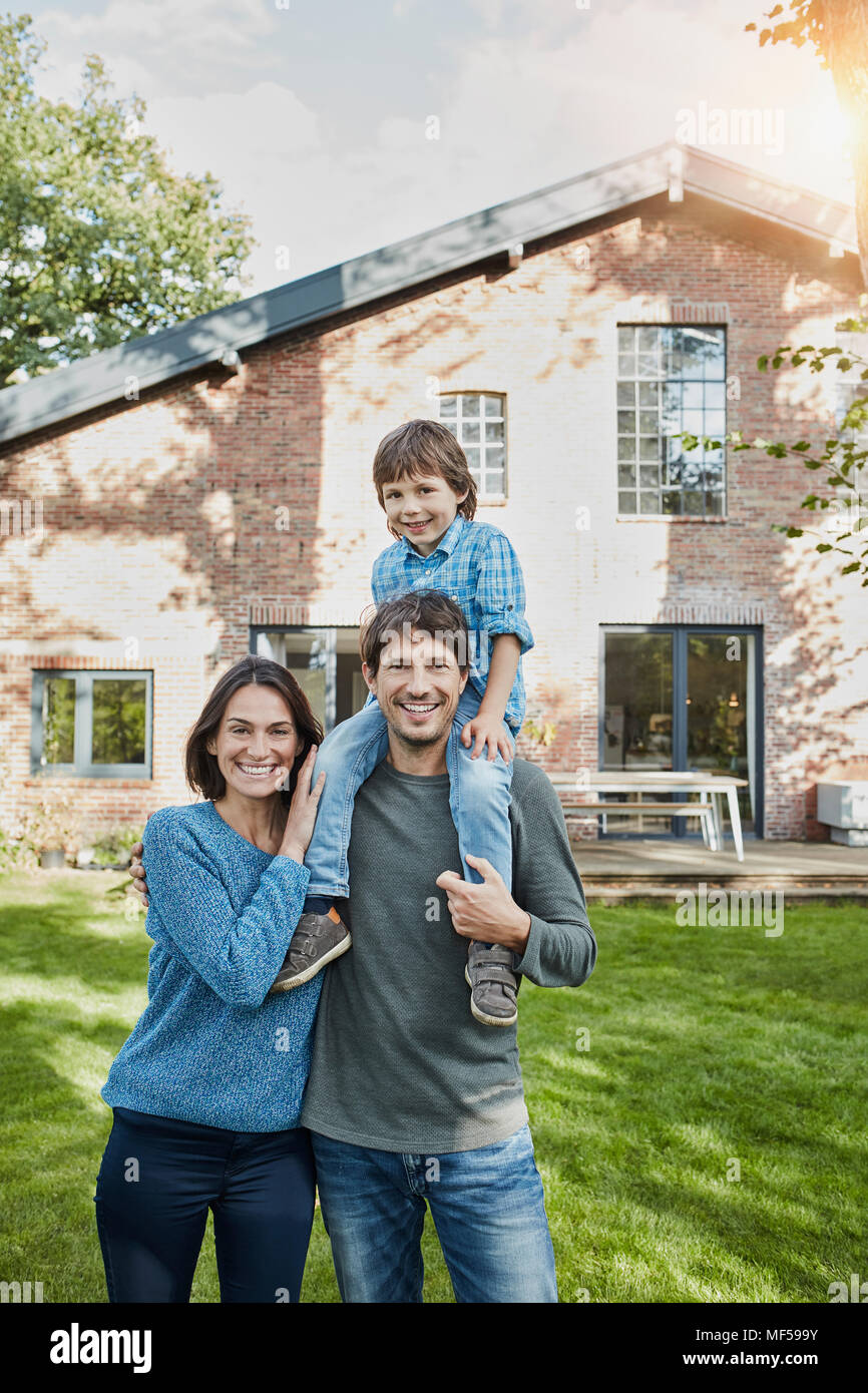 Portrait of happy family with son in garden of their home - Stock Image