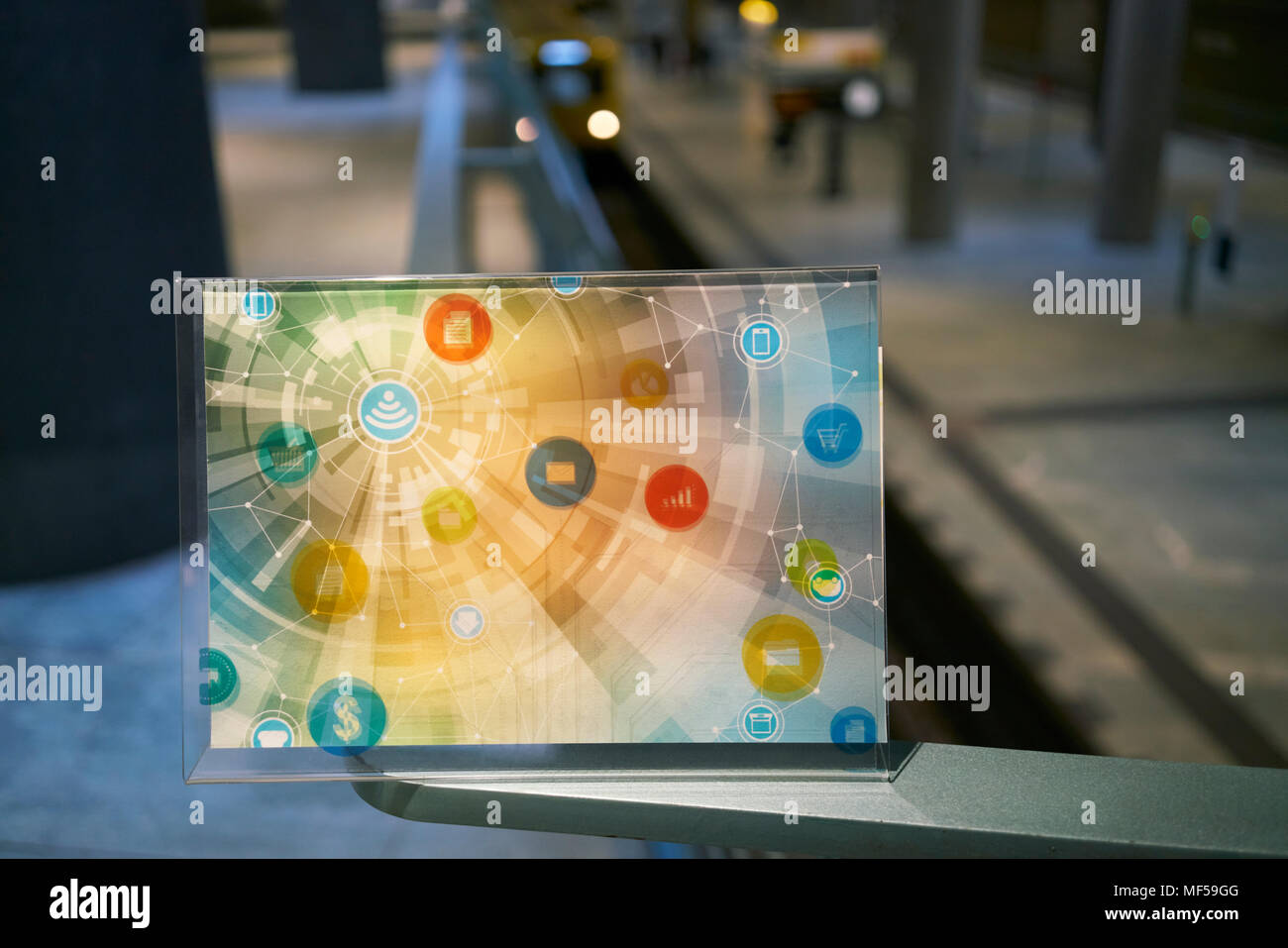 Futuristic device with digital icons at underground station in the city - Stock Image