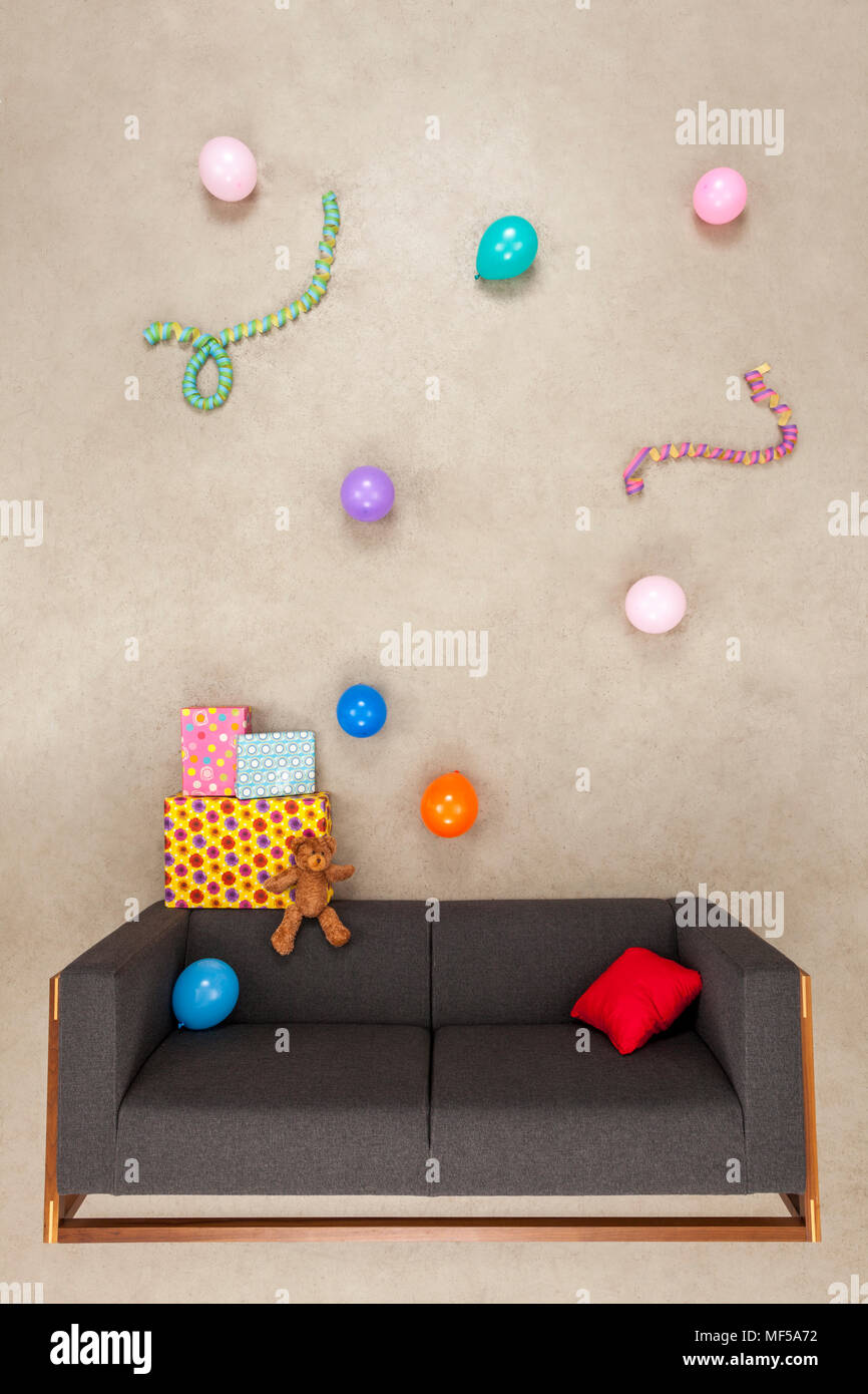 Ballons and streamers with presents on a couch - Stock Image