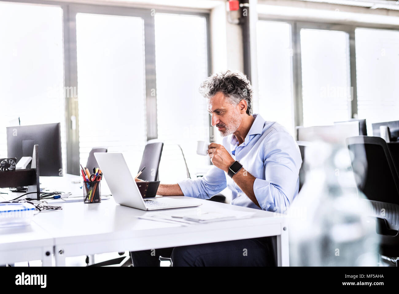 Mature businessman sitting at desk in office using laptop and drinking coffee - Stock Image