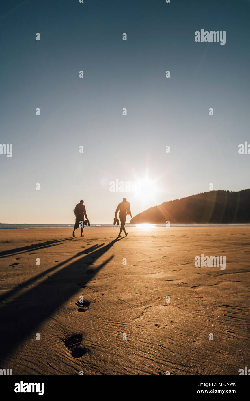 Canada, British Columbia, Vancouver Island, two men walking on beach at San Josef Bay at sunset - Stock Image