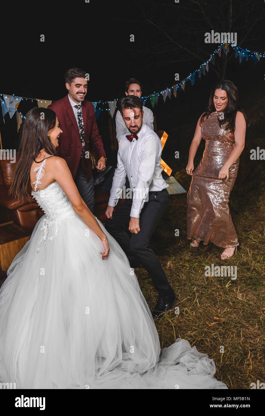 Happy bride dancing and having fun with her friends on a night field party - Stock Image