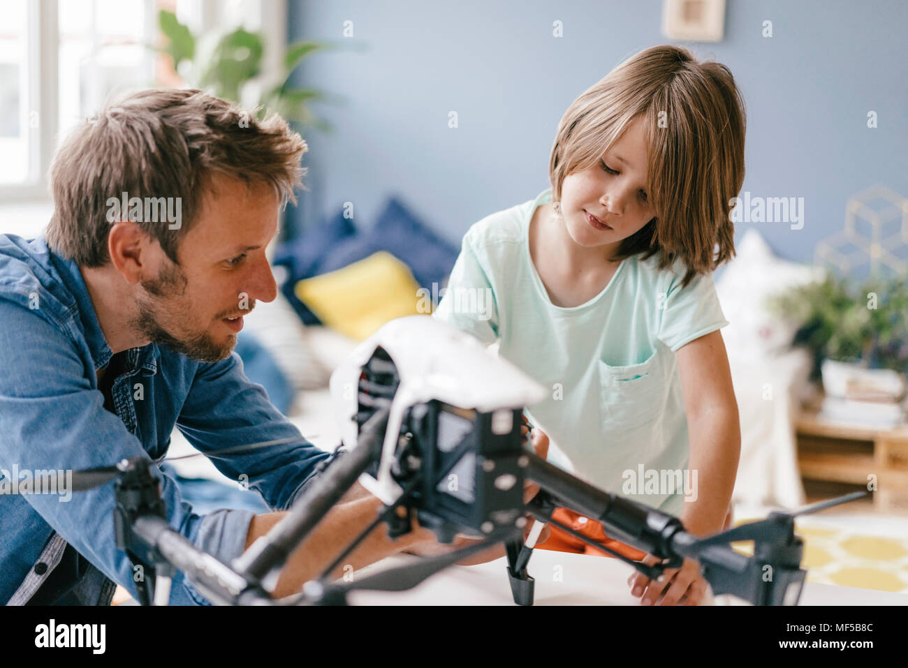 Father and son with drone at home - Stock Image