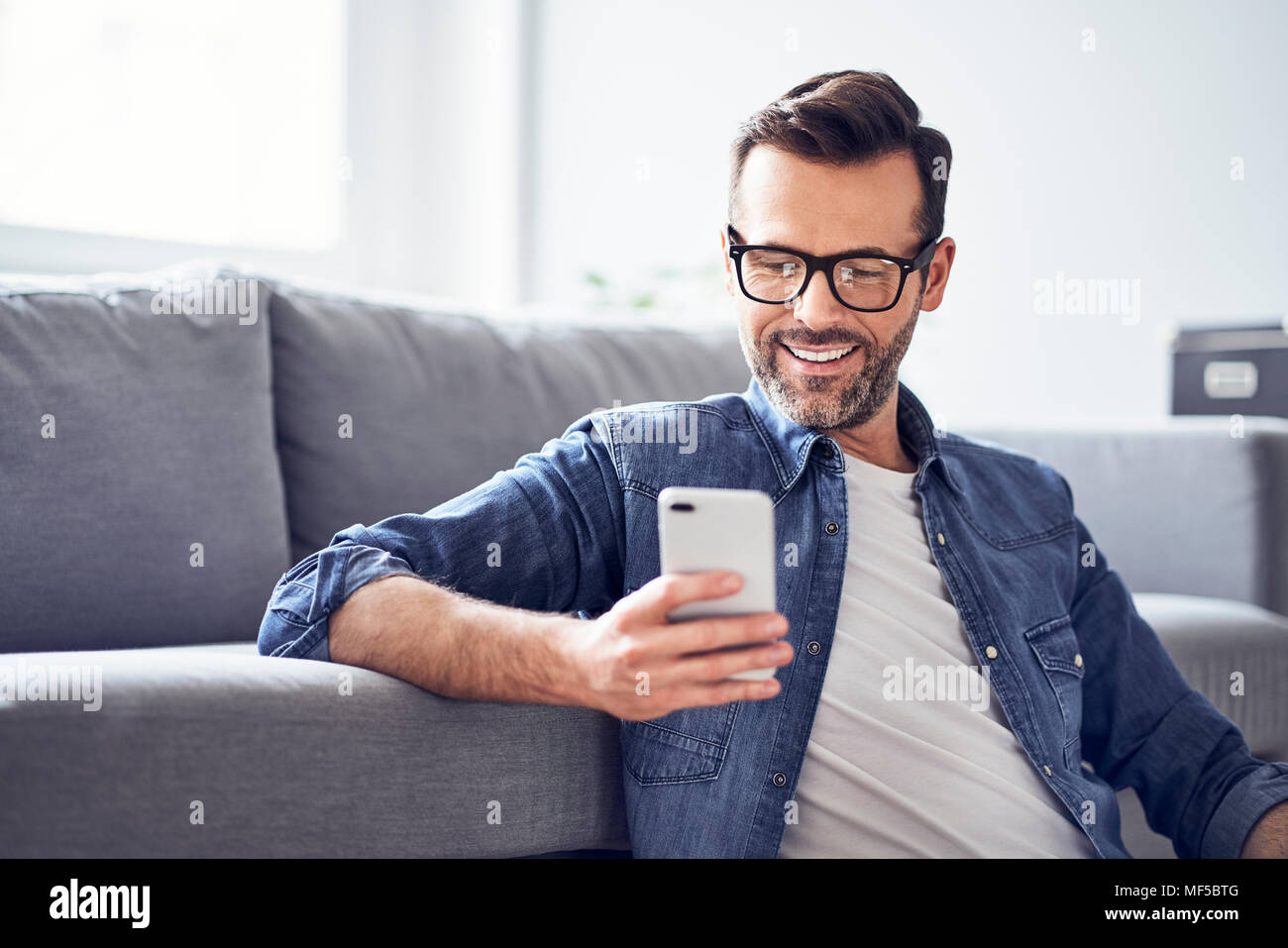 Smiling man in living room looking at cell phone - Stock Image