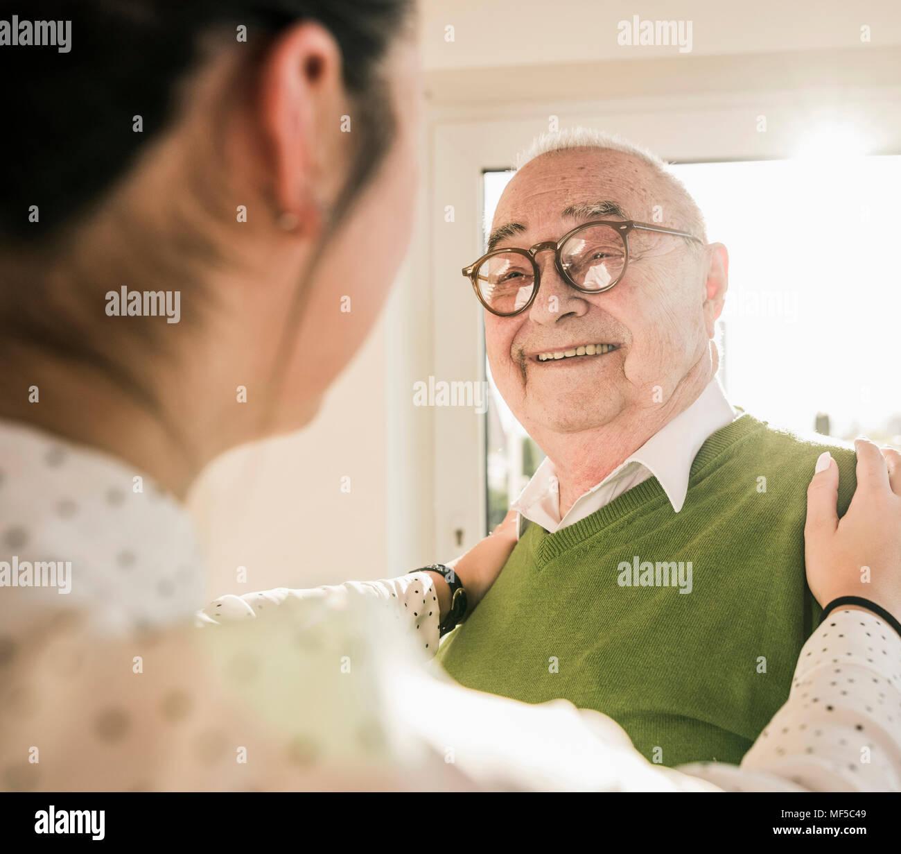 Senior man smiling at young woman - Stock Image
