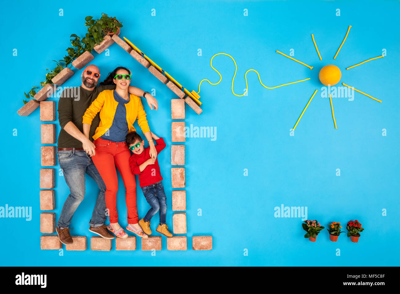 Happy family standing in house, with solar panels plugged to sun - Stock Image