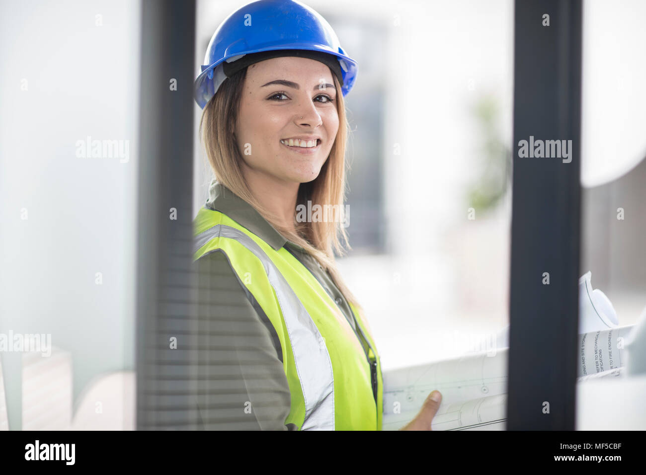 Portrait of smiling woman wearing hard hat and reflective jacket - Stock Image