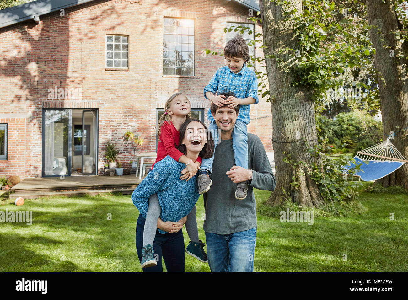 Portrait of happy family in garden of their home Stock Photo