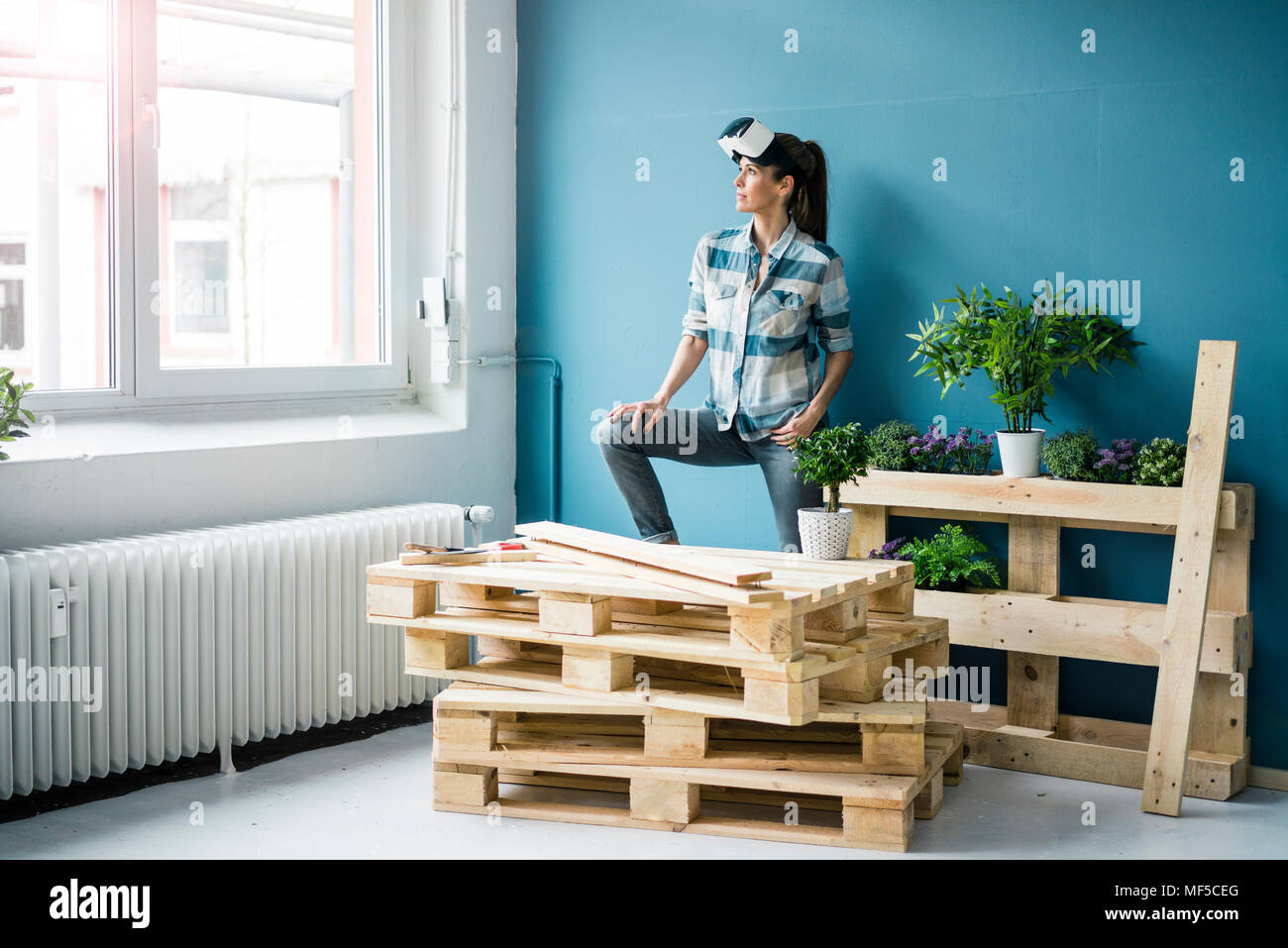 Woman using VR glasses, renovating her new home - Stock Image