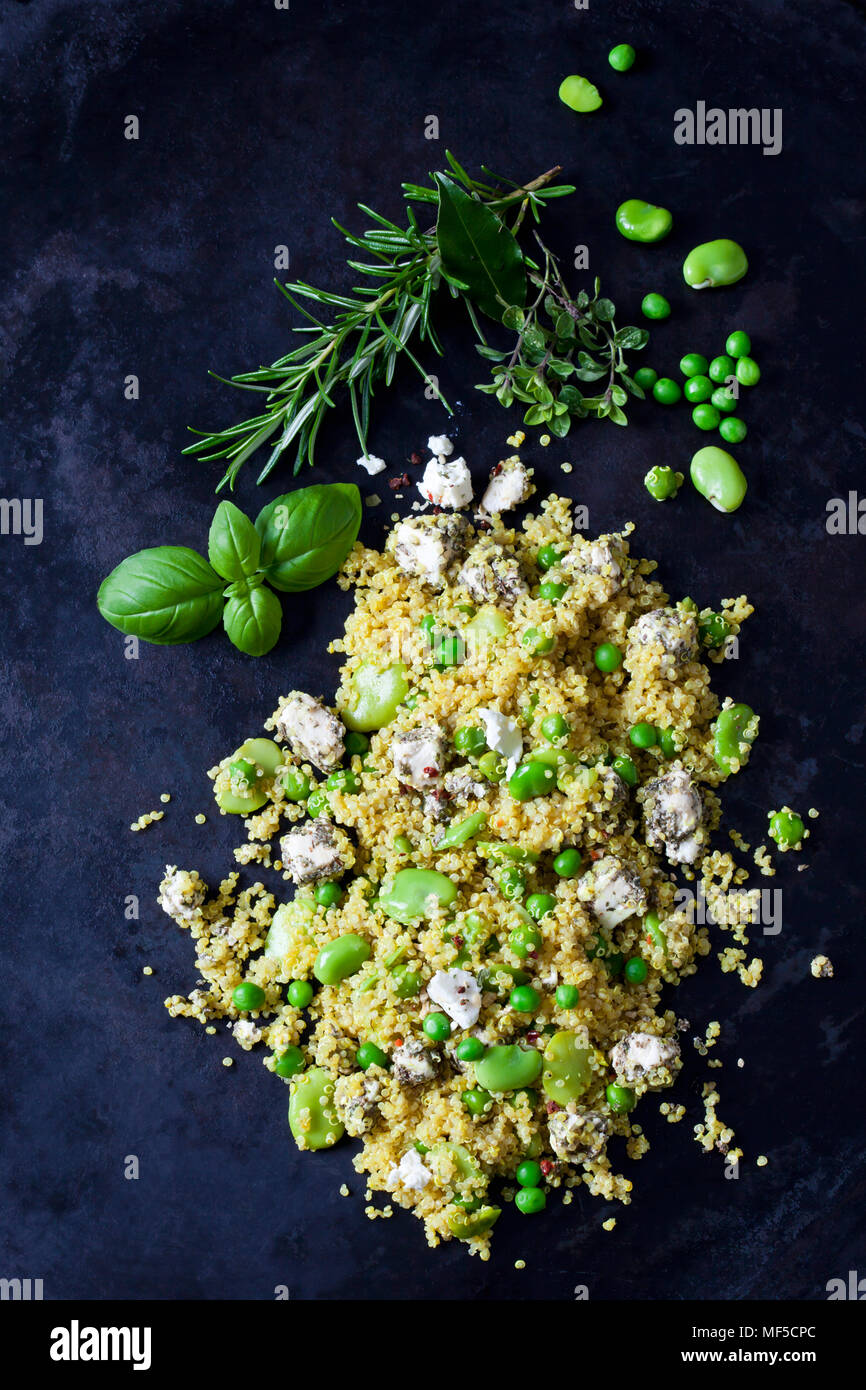 Quinoa salad with broad beans, peas and feta on dark metal - Stock Image
