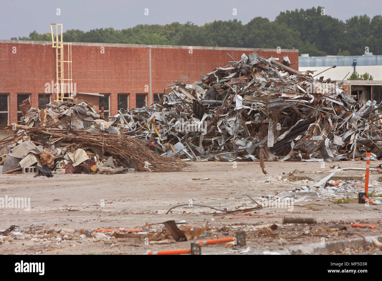 Debris piles of twisted metal and junk are stacked high at the demolition site of an auto assembly plant - Stock Image