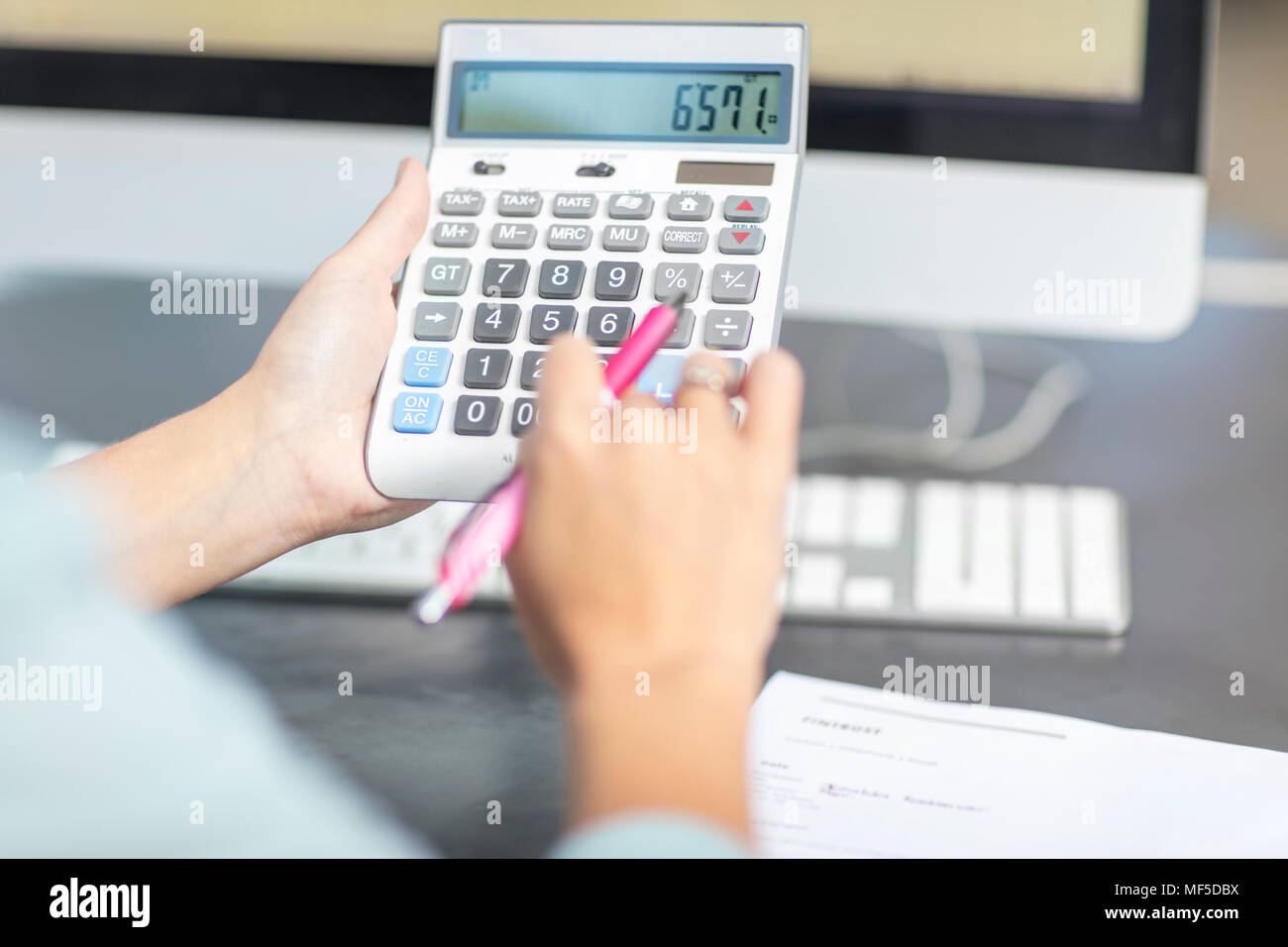 Woman at desk in office using calculator Stock Photo