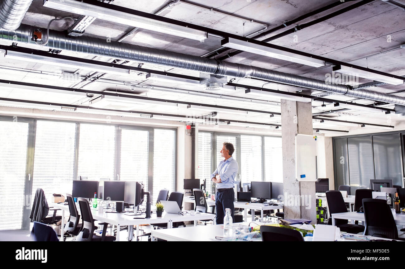 Mature businessman standing in open plan office - Stock Image