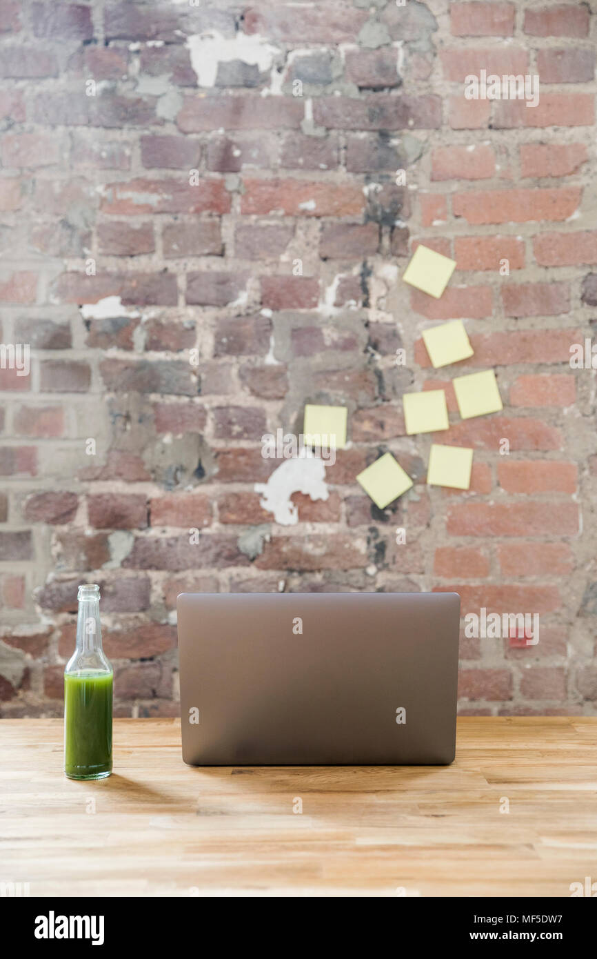 Glass bottle of green smoothie and laptop on wooden tabletop in a loft - Stock Image