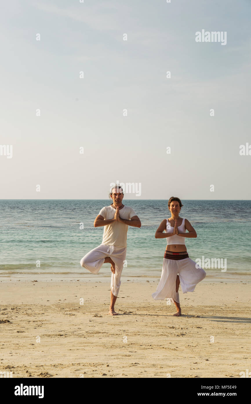 Thailand, Koh Phangan, couple doing yoga on a beach - Stock Image
