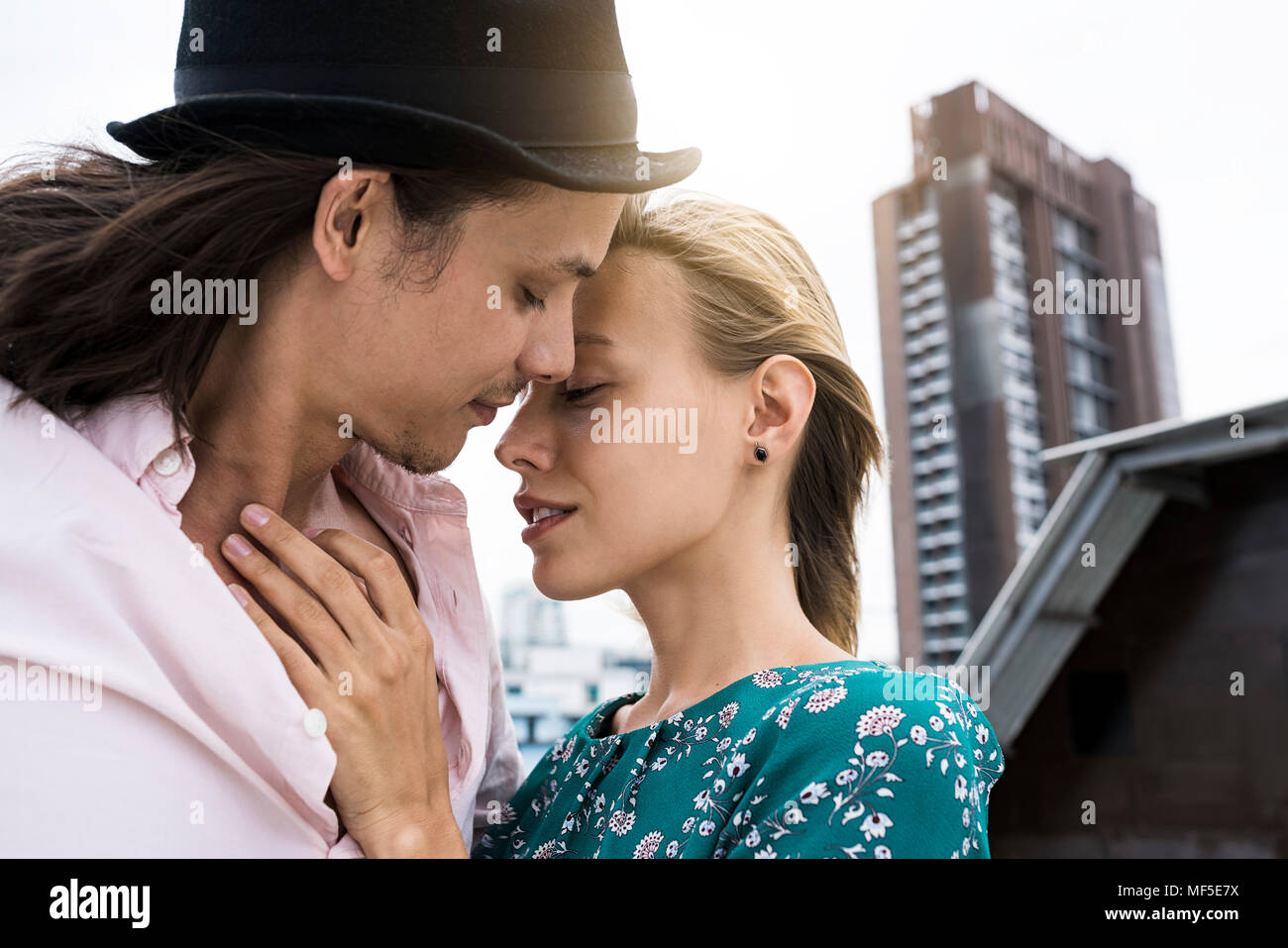 Young affectionate couple kissing on rooftop - Stock Image