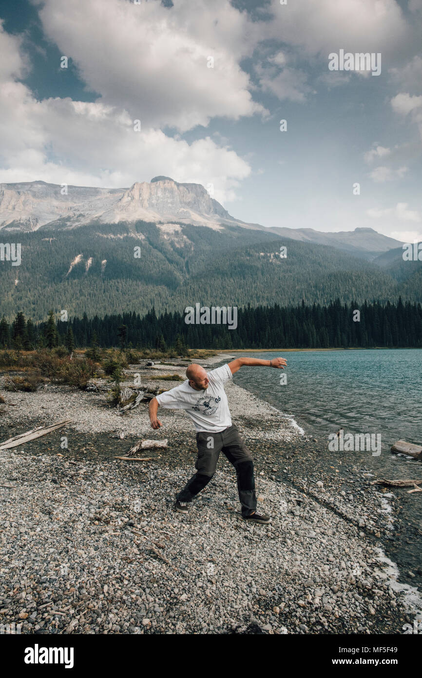 Canada, British Columbia, Yoho National Park, man skipping stones at Emerald Lake - Stock Image