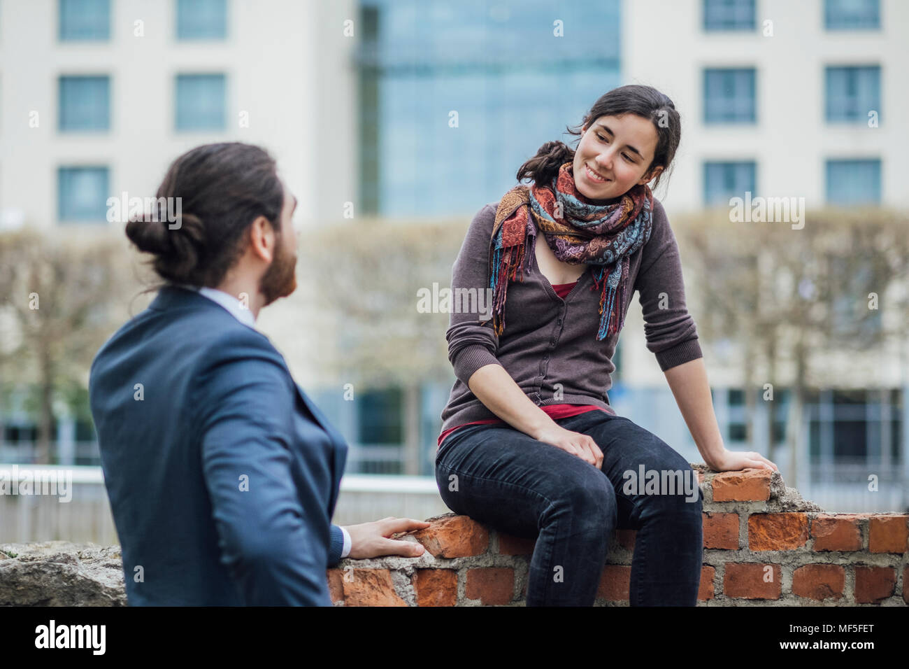 Woman sitting on a wall outside office building smiling at businessman - Stock Image