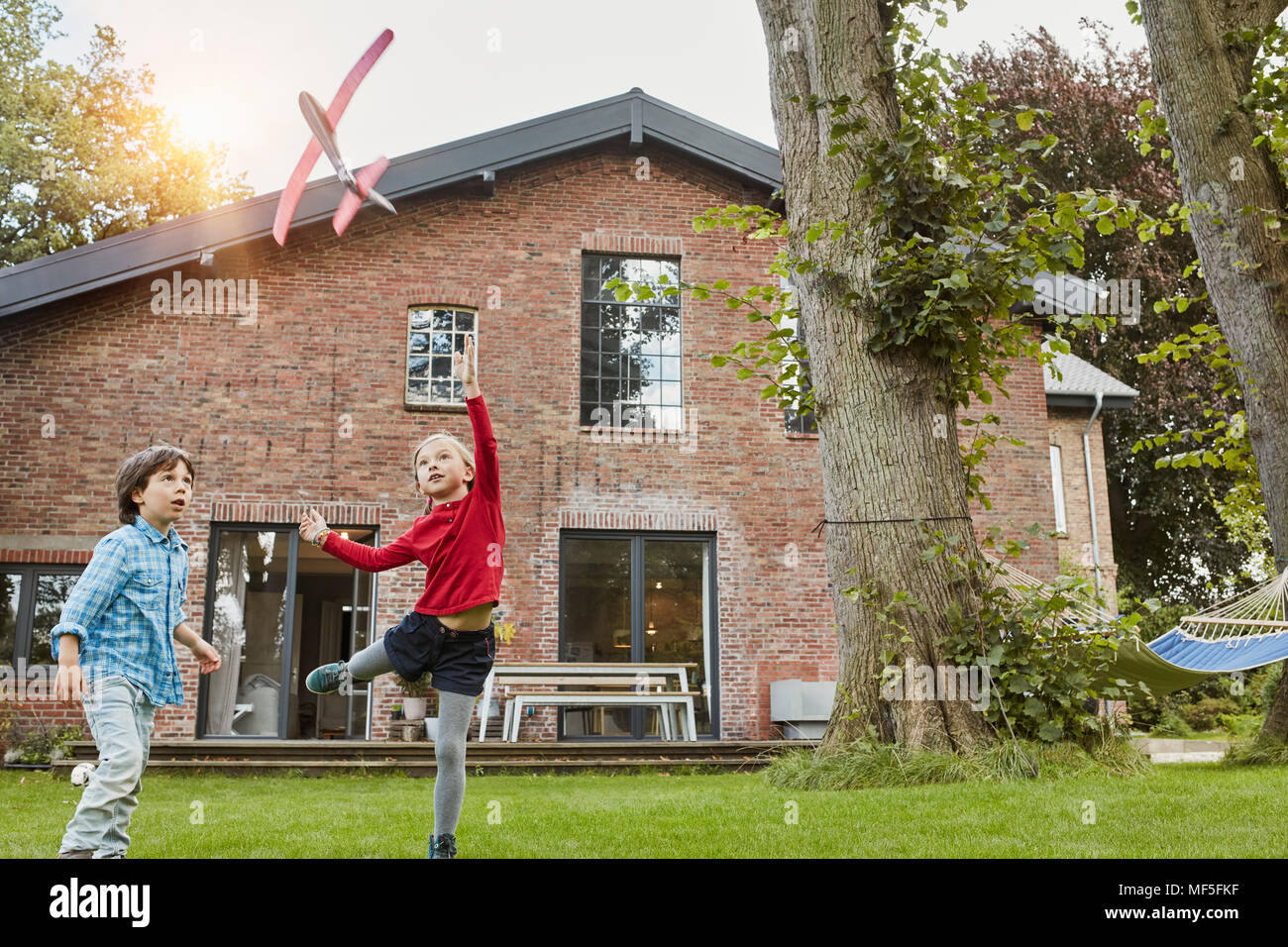 Two children playing with toy airplane in garden of their home - Stock Image
