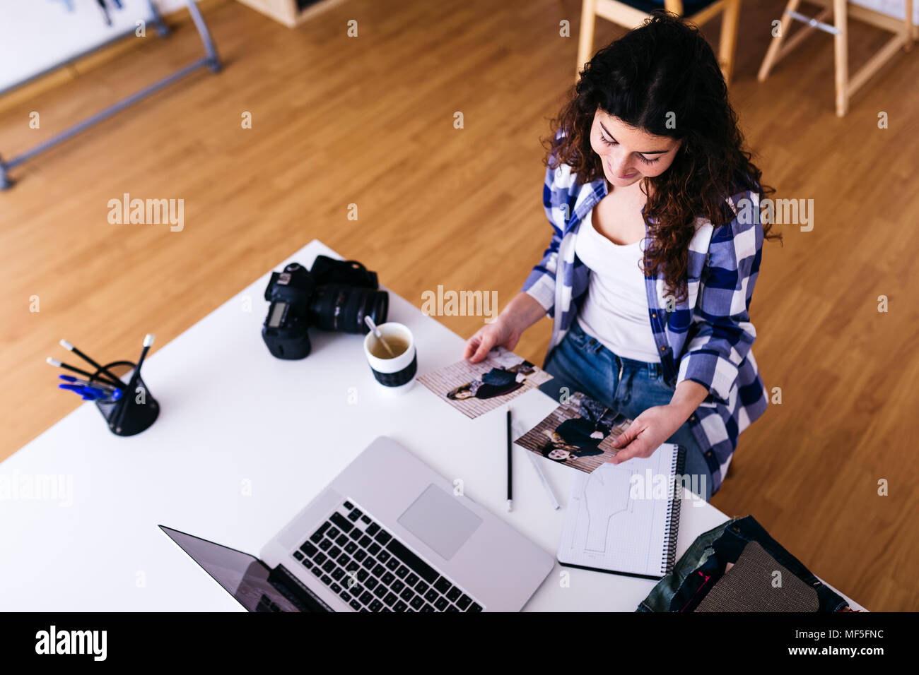 Fashion designer with laptop looking at photos in studio - Stock Image