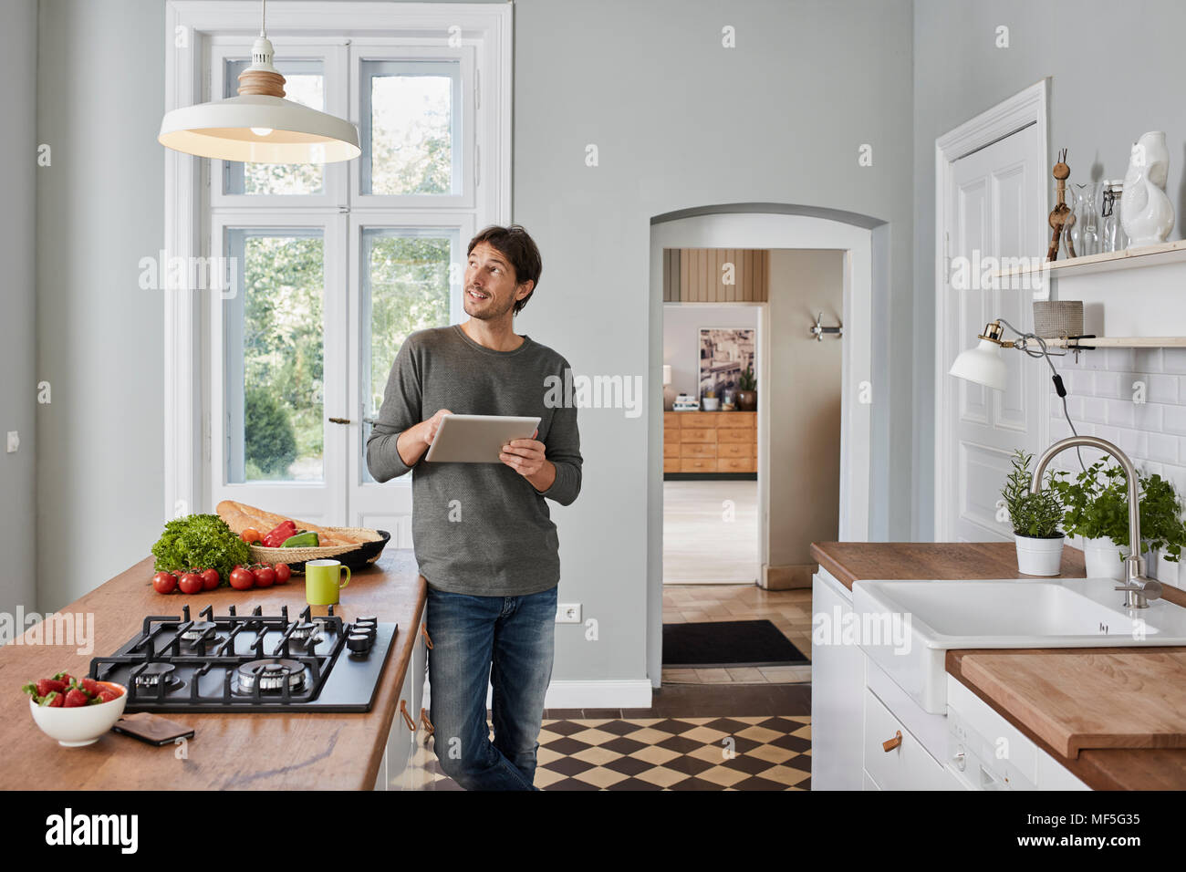 Man using tablet in kitchen looking at ceiling lamp - Stock Image