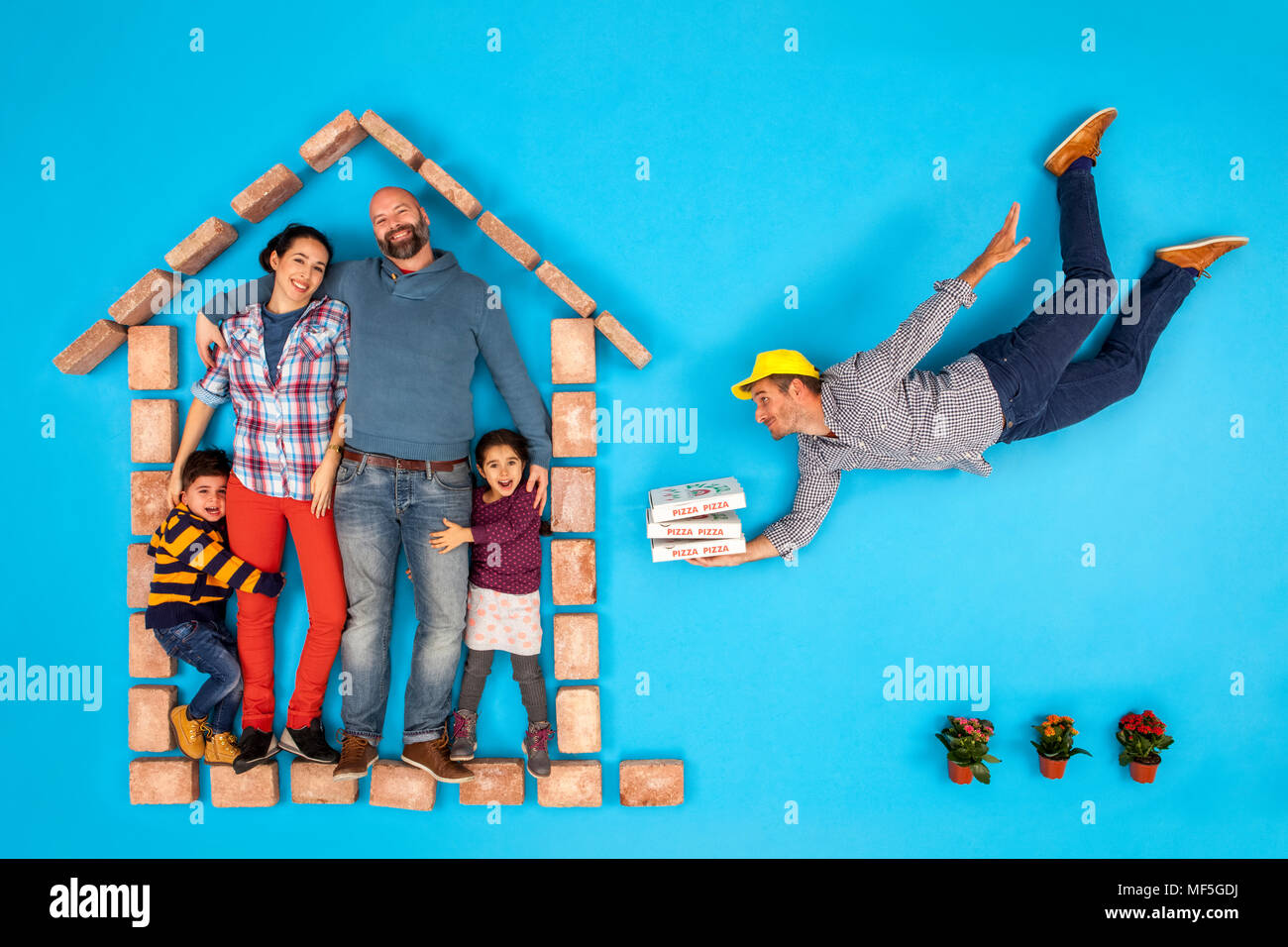 Happy family at home getting pizza delivered - Stock Image