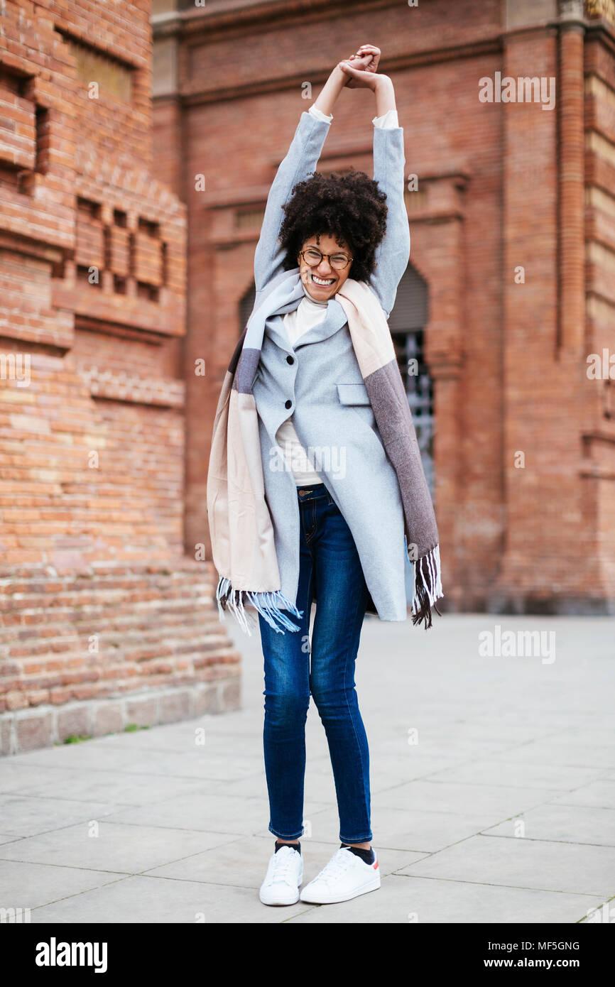Portrait of exuberant woman standing at brick building - Stock Image