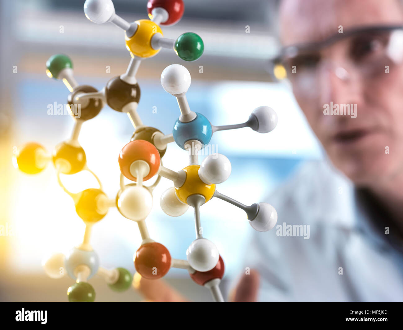 Scientist looking at molecular model - Stock Image