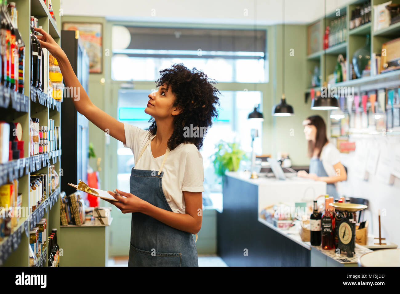 Woman with clipboard at shelf in a store - Stock Image