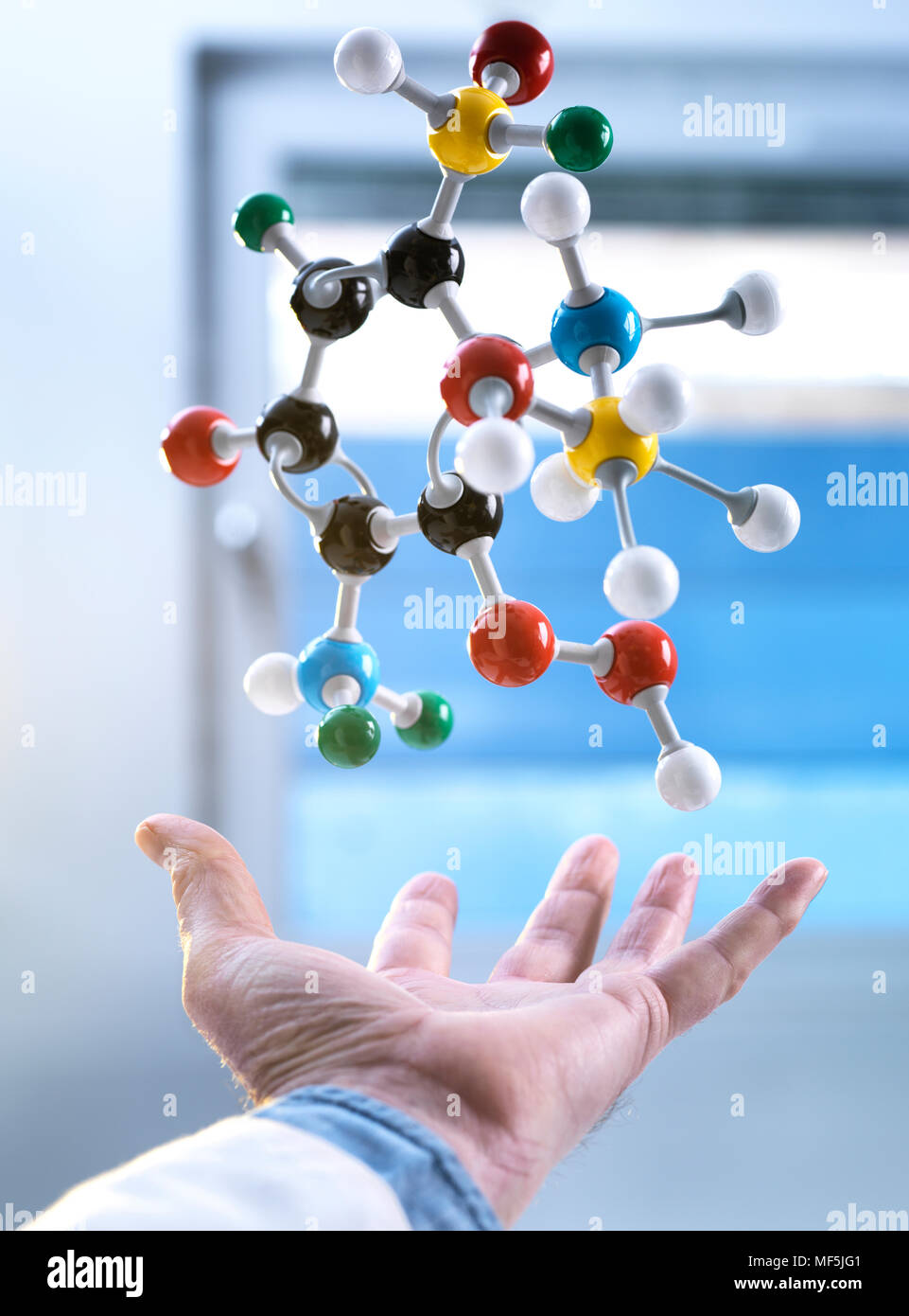 Hand and a floating molecular model, gravity - Stock Image