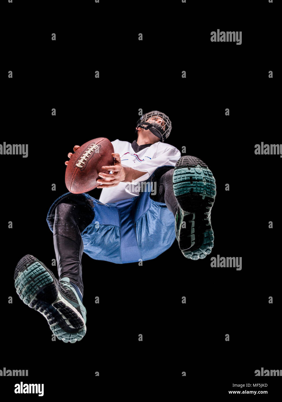 Athlete playing football, view from below - Stock Image
