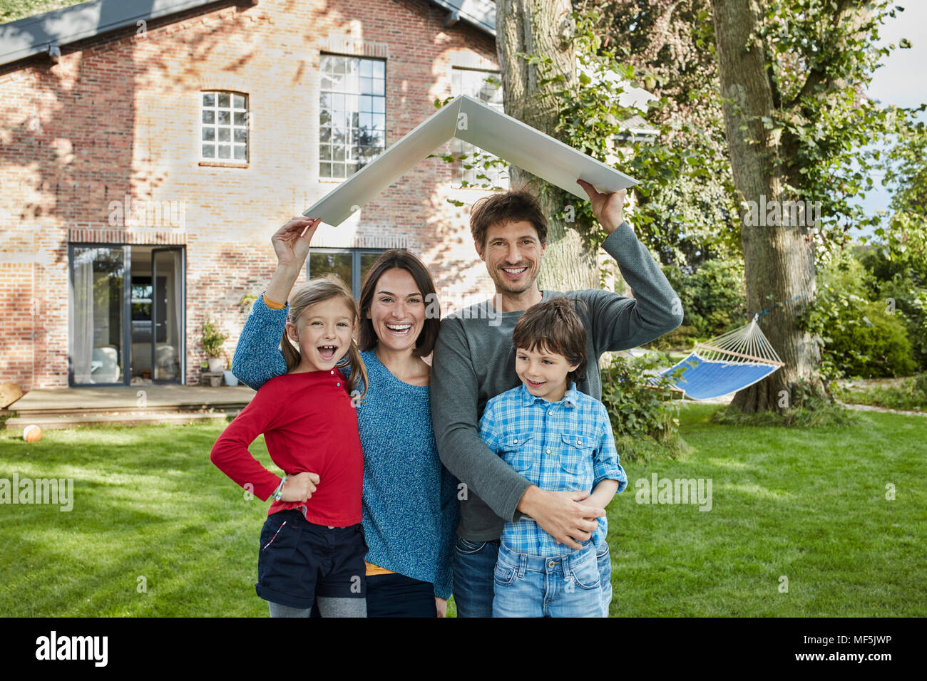 Portrait of happy family in garden of their home holding roof - Stock Image