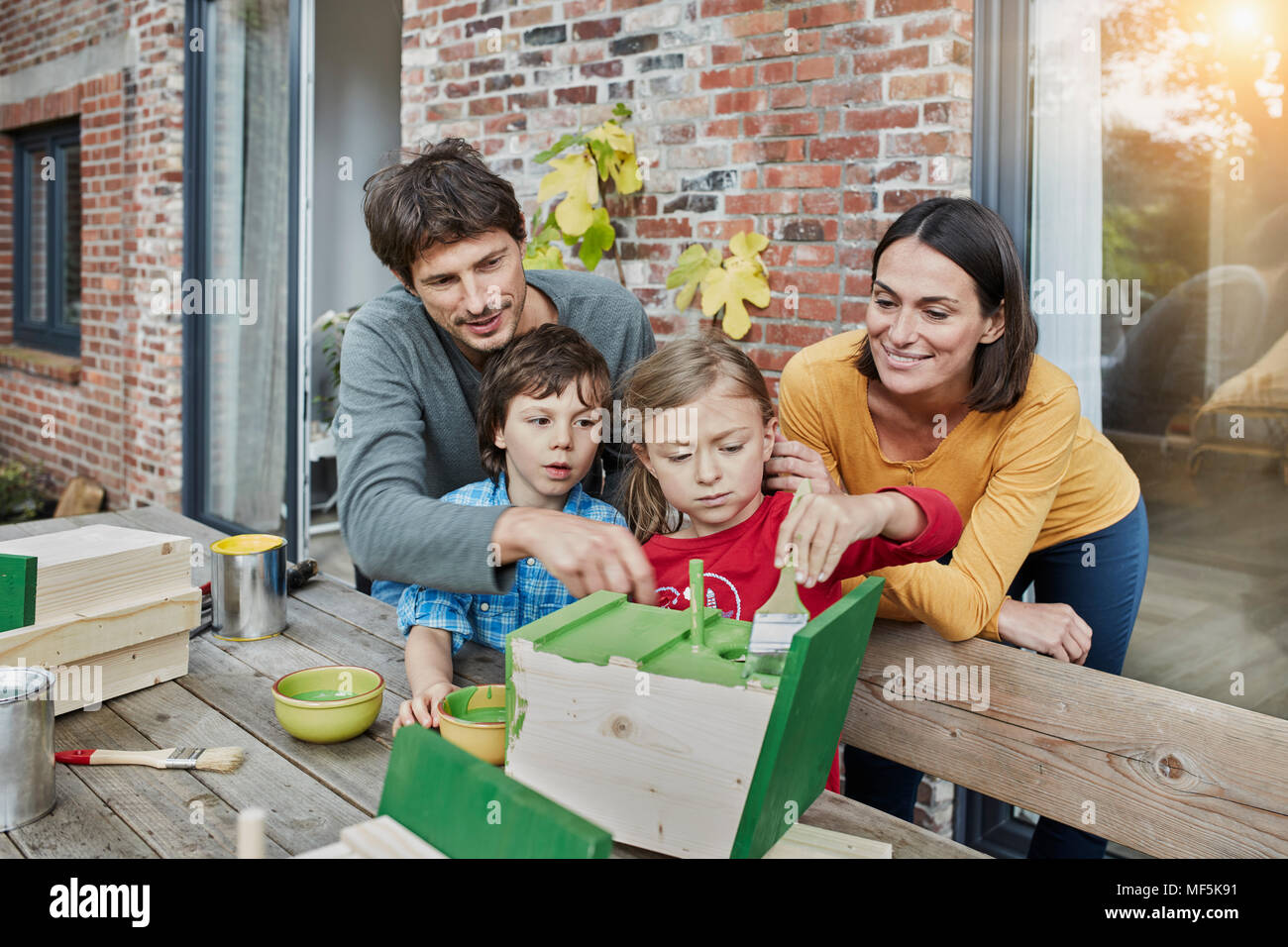 Family working on birdhouse in front of their home - Stock Image
