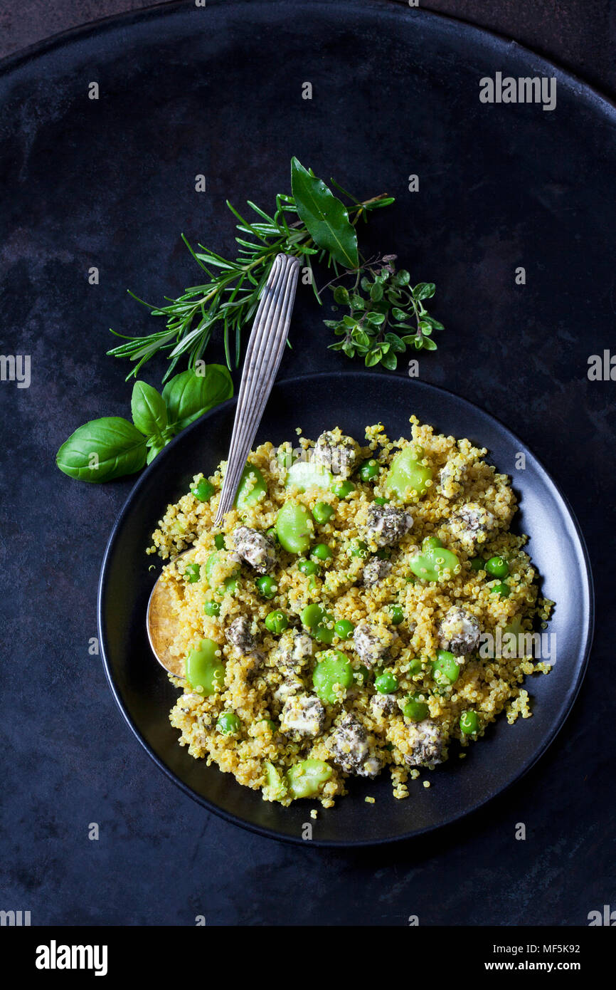 Bowl of quinoa salad with broad beans, peas and feta - Stock Image