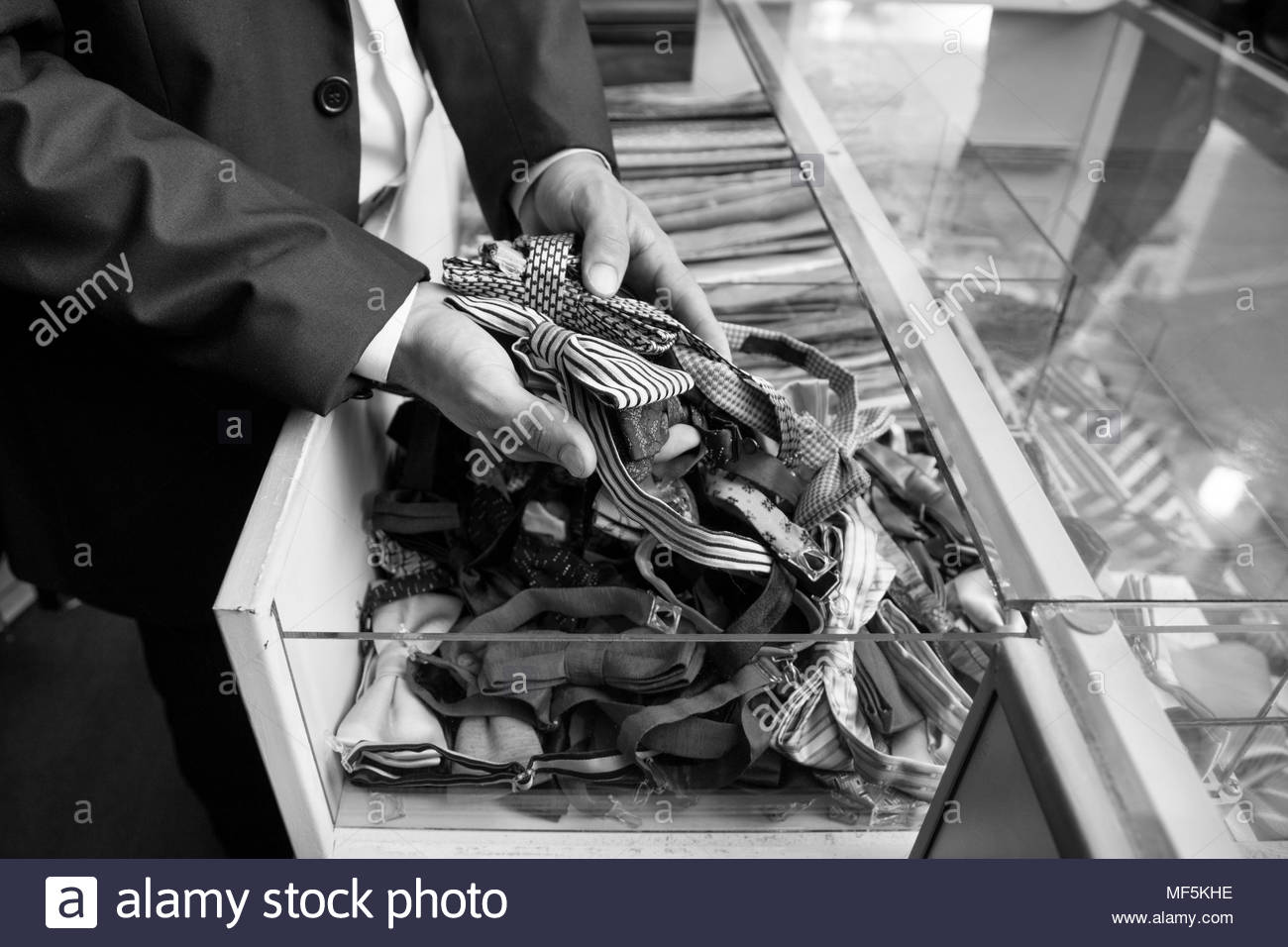 Tailor tidying up ties in glass case - Stock Image