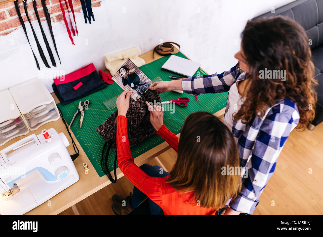 Two fashion designers in studio looking at photography - Stock Image