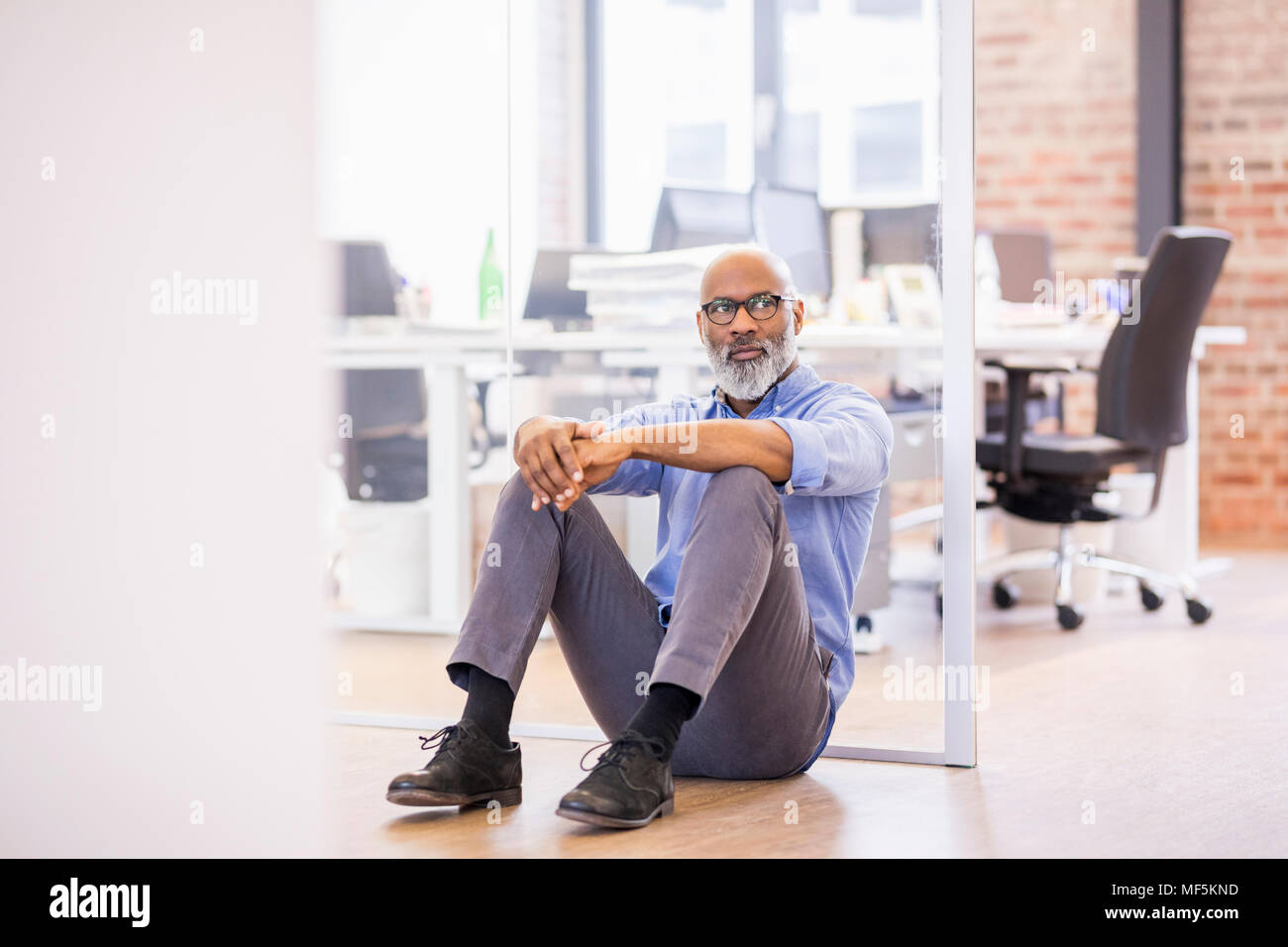 Portrait of businessman sitting on the floor of an office - Stock Image